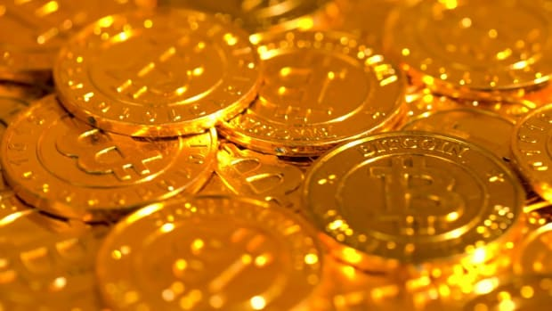 videoblocks-a-pile-of-bitcoin-rotating-on-a-shiny-golden-background_bh8qmzysg_1080__D