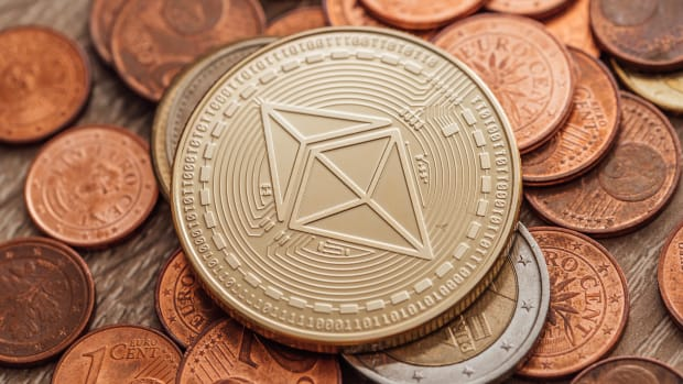 Close-up of a physical Ethereum coin on a bunch of fiat coins.
