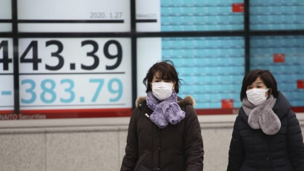 Pedestrians pass a stock board of a securities firm in Tokyo on Monday, when shares tumbled in the few Asian markets open as China announced sharp increases in the number of people affected in the coronavirus outbreak. Photo: AP