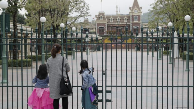 A family stands at the closed gates of Disneyland. Photo: Edmond So