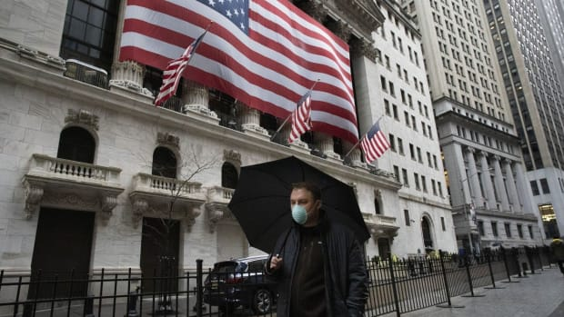 A man wearing a mask walks by the New York Stock Exchange, on Tuesday. Photo: AP Photo
