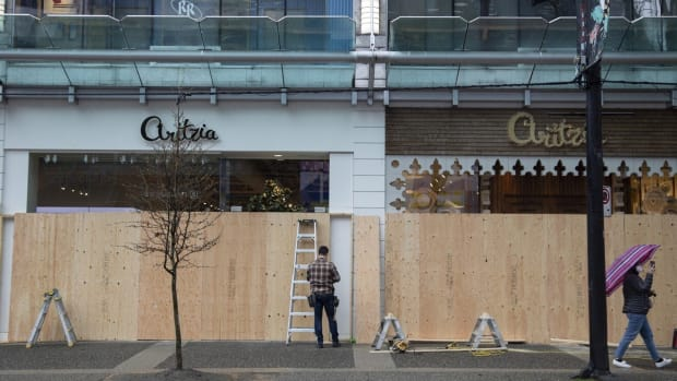 Workers board up an Aritzia clothing store on Robson Street in Vancouver on March 27. Photo: Bloomberg