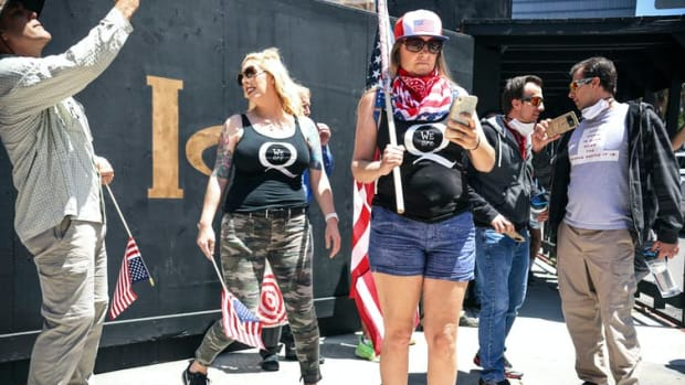 QAnon demonstrators protest during a rally to reopen California and against stay-at-home directives on May 1, 2020, in San Diego.
