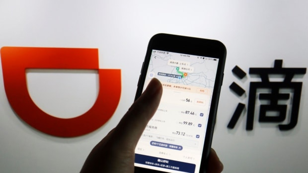 The app of Chinese ride-hailing giant Didi is seen on a mobile phone in front of the company logo. Photo: Reuters