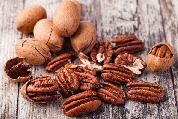 AlabamaPecans, blackberries, Lane cake, Conecuh Ridge whiskey Pecans are native to North America. Alabama produces an average of about 6.8 million pounds ofthe nuts a year. Lane cake is a layered cake often filled with pecans, coconut, and raisins soaked in whiskey.Photo: Shutterstock