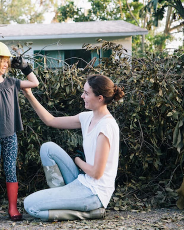 A mother and daughter work to clear debris near their home after a hurricane.