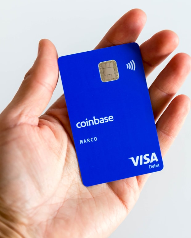 Photo of hand holding Coinbase debit card.