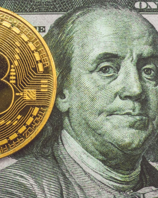 Image of physical Bitcoin against US 100 dollar bill.