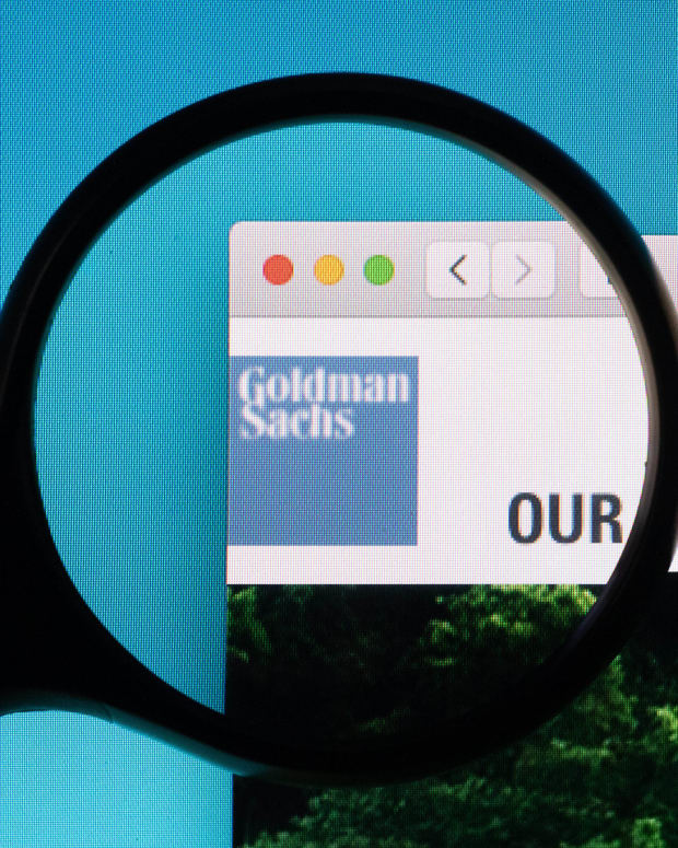 Goldman Sachs website logo under a magnifying glass.