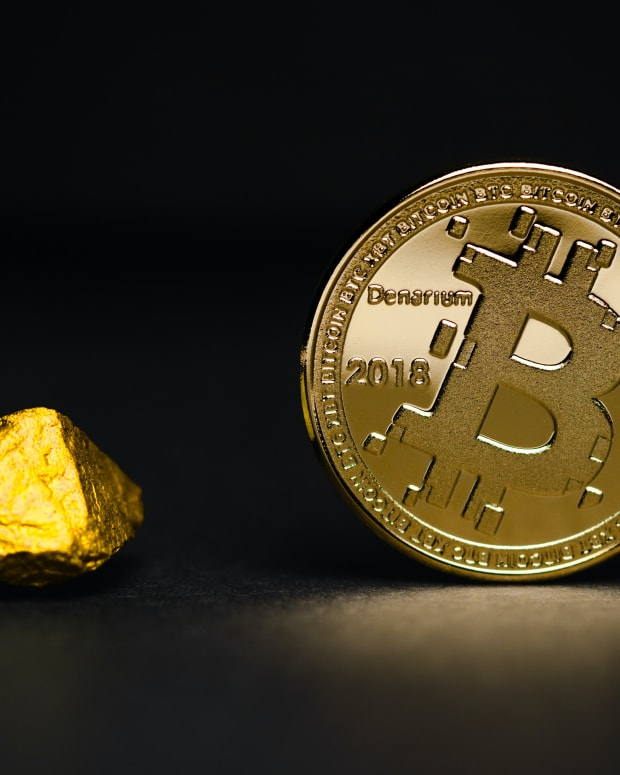Lump of gold and a golden physical Bitcoin next to each other.
