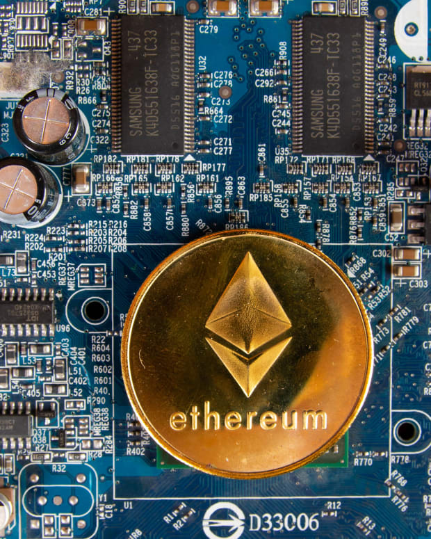 Coin with Ethereum logo on motherboard.