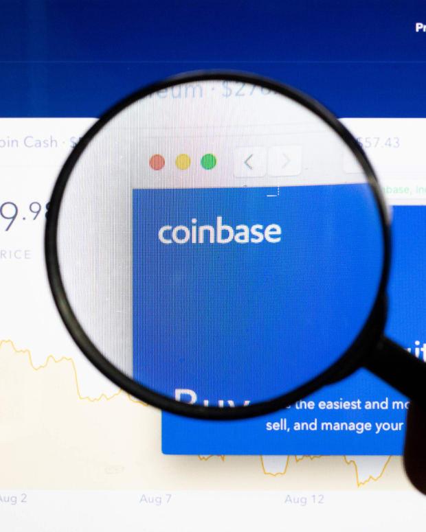 Coinbase logo under a magnifying glass.