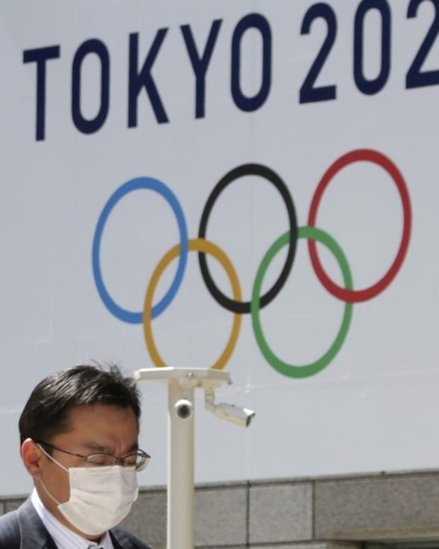 A masked man walks in front of a Tokyo Olympics logo at the Tokyo metropolitan government headquarters building in Tokyo on March 25, 2020. Photo: AP