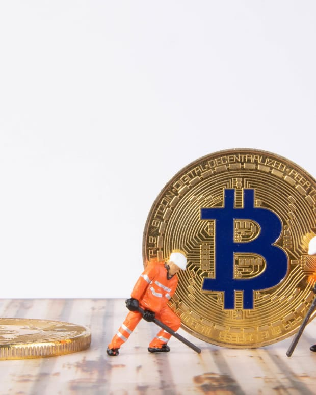 Toy figures hold mining equipment in front of physical bitcoin.