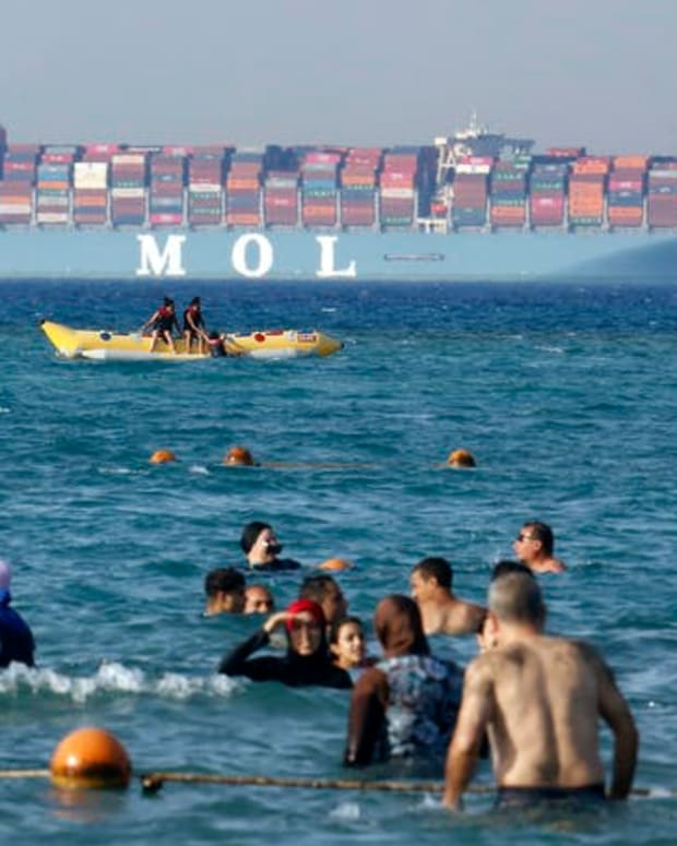 Beachgoers near Cairo watch a massive container ship sail to the Red Sea.