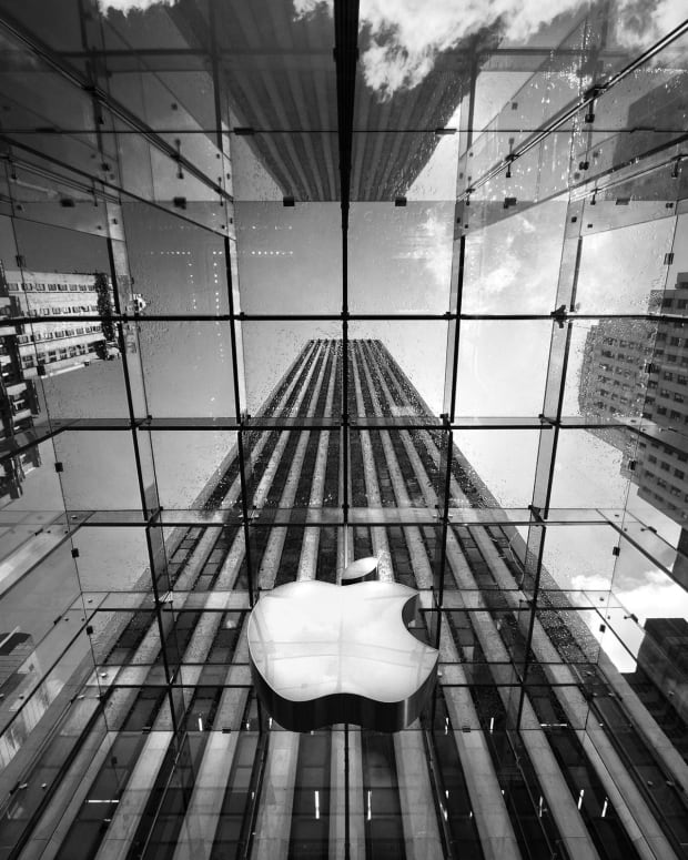 apple-logo-in-middle-of-building-under-the-rain-2K-wallpaper