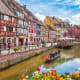 "Colmar, FranceLocal speciality: Alsace wineMedieval houses line the water in France's ""Little Venice,"" where you can roam cobblestone streets and sip wine in a cafe.Photo: Shutterstock"