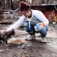 A month after the Camp Fire, Mary Gowins feeds a neighborhood cat she has taken care of for the past seven years in Paradise, Calif. The cat had been lost since the fire erupted on Nov. 8, 2018.Photo: Staff Sgt. Taylor Workman/USAF