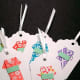 Materials: Plain paper tags with string http://www.amazon.com/Company-String-Hangers-4-Inch-Package/dp/B001CRI6II , origami paper. Instructions: There are countless ways to decorate your own gift tags. If your kids are young, stick to glue, glitter, markers, and the like. But if your kids are a bit older, you could make more sophisticated tags like the ones pictured. No need to buy an origami book – there are lots of how-to guides online. Photo Credit: kittykatkards