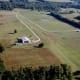 In the bucolic and beautiful countryside about 30 minutes south of Nashville, TN, a quartet of large lots have exclusive access to an FAA approved 2,400 foot long turf runway. One of the lots, a 21.15-acre spread listed at $539,000, includes a private home, vast hangar, workshop and 1,000 sq. ft. equipment storage building. Photo Credit: Joe Roberts, owner
