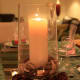 A large candle placed inside an even larger hurricane glass vase is my favorite centerpiece. It lights up the dinner table not only during the holidays, but all year long. To quickly transform it into a holiday centerpiece, I surrounded the vase with ornaments, pine cones – and more candles in different sizes.