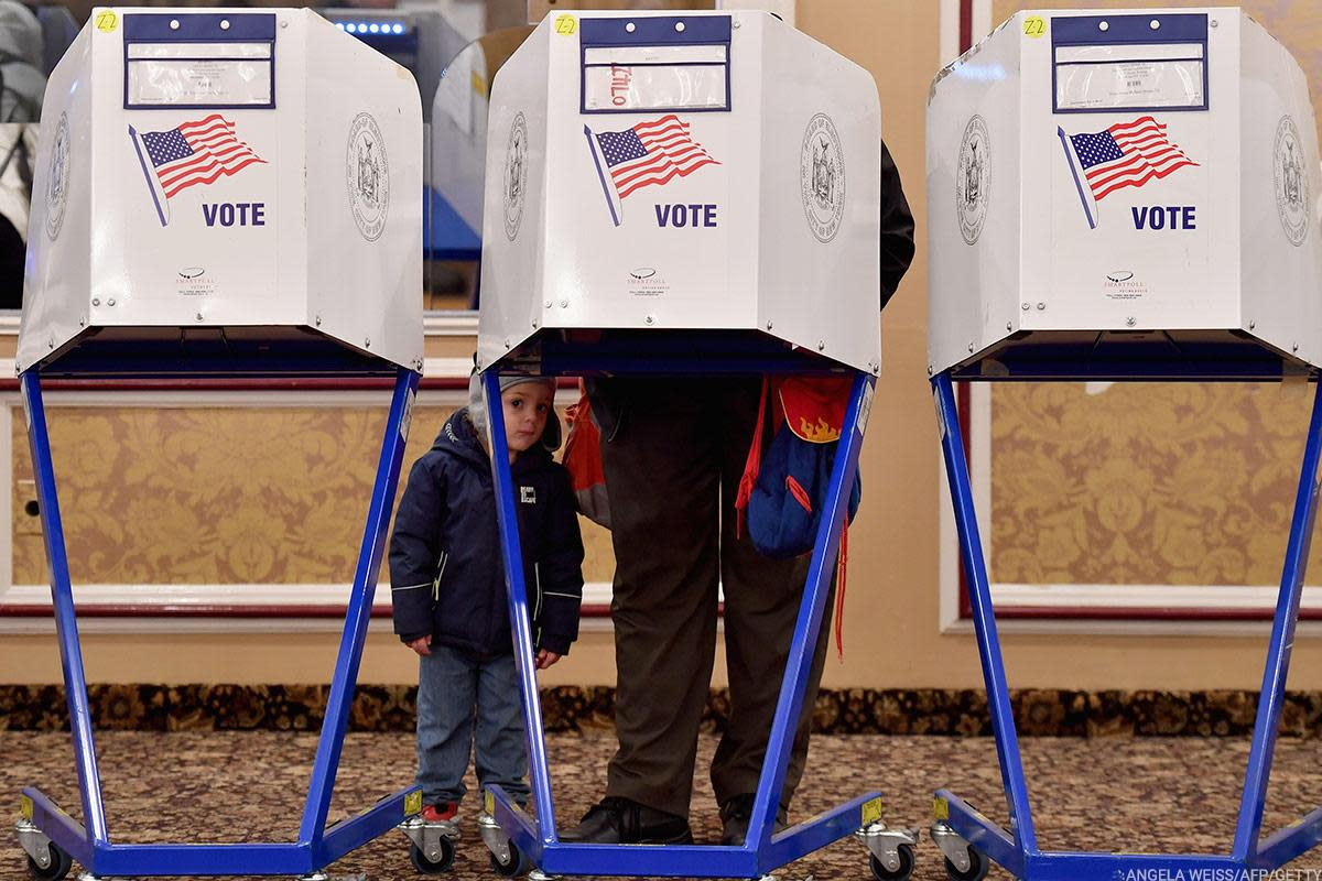 A voter takes a small child to the polls Tuesday as Americans across the country choose House members, senators, governors and more.