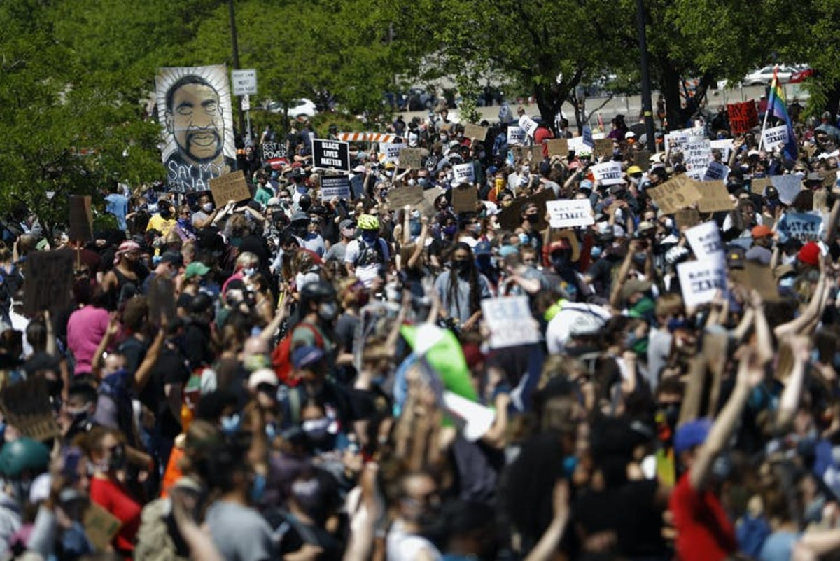 People gather for a rally in Minneapolis following the death of George Floyd. George Soros has long been a target of conspiracy theories and is now being falsely accused of orchestrating and funding the protests over police killings of Black people that have roiled the United States. (AP Photo/Julio Cortez)