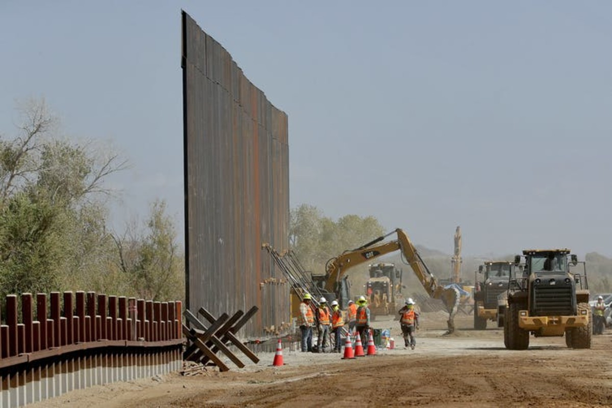 In this September 2019 photo, government contractors erect a section of the border wall along the Colorado River in Yuma, Ariz. (AP Photo/Matt York)