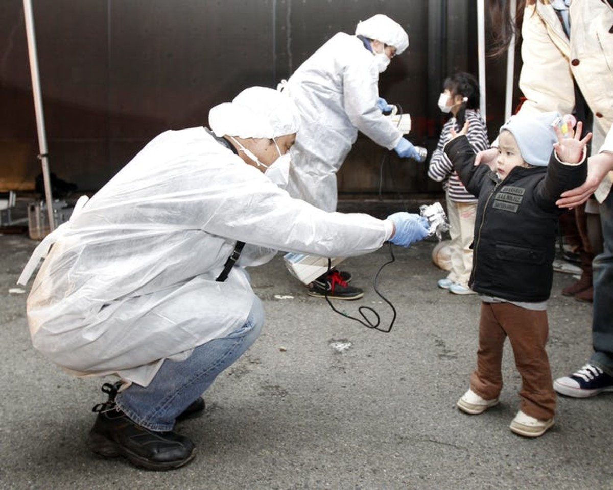 Officials in protective gear check for signs of radiation on children who are from the evacuation area near the Fukushima Daini nuclear plant in Koriyama in this March 13, 2011 photo. Reuters/Kim Kyung-Hoon/Files