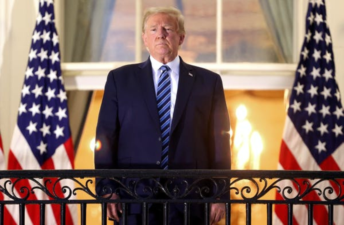 Trump stands, maskless, on the Truman Balcony after returning to the White House. Win McNamee/Getty Images)
