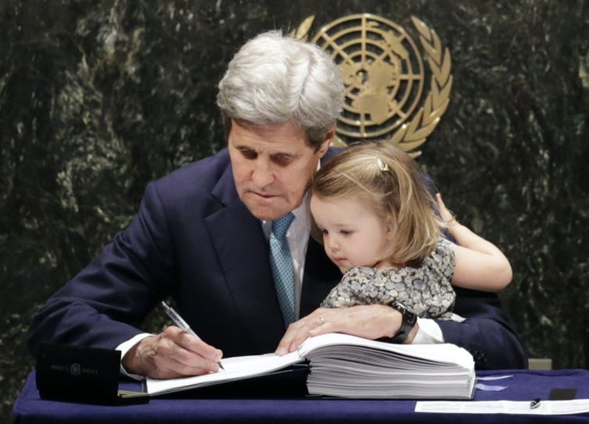 Then-Secretary of State John Kerry held his granddaughter as he signed the Paris climate agreement in 2016. AP Photo/Mark Lennihan