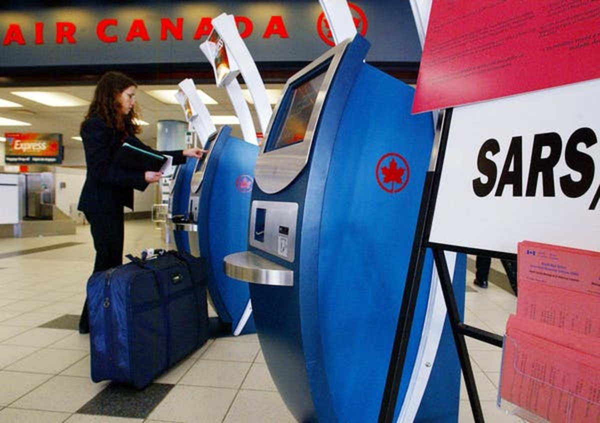 A passenger checks in as a warning sign gives information about SARS at Pearson International Airport on May 30, 2003. CP PHOTO/Kevin Frayer