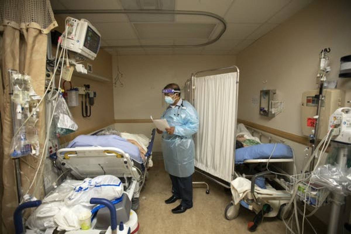 A doctor checks on patients in a temporary space at an overloaded hospital near Los Angeles. Francine Orr/Los Angeles Times via Getty Images