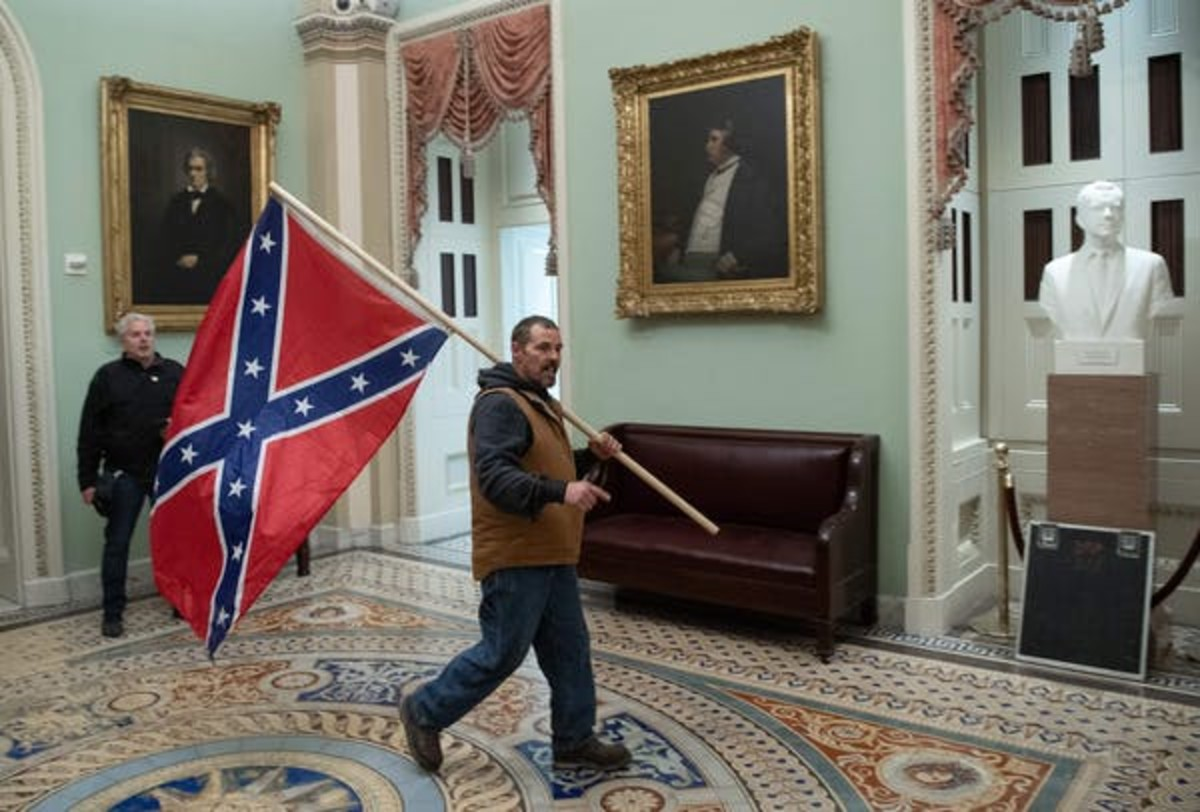 A man carries the Confederate battle flag in the U.S. Capitol on Jan. 6, between portraits of senators who both opposed and supported slavery. Saul Loeb/AFP via Getty Images