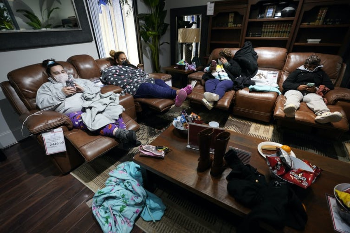 People with no power at their homes rest inside a Gallery Furniture store in Houston after the owner opened the business as a shelter on Feb. 16, 2021. AP Photo/David J. Phillip