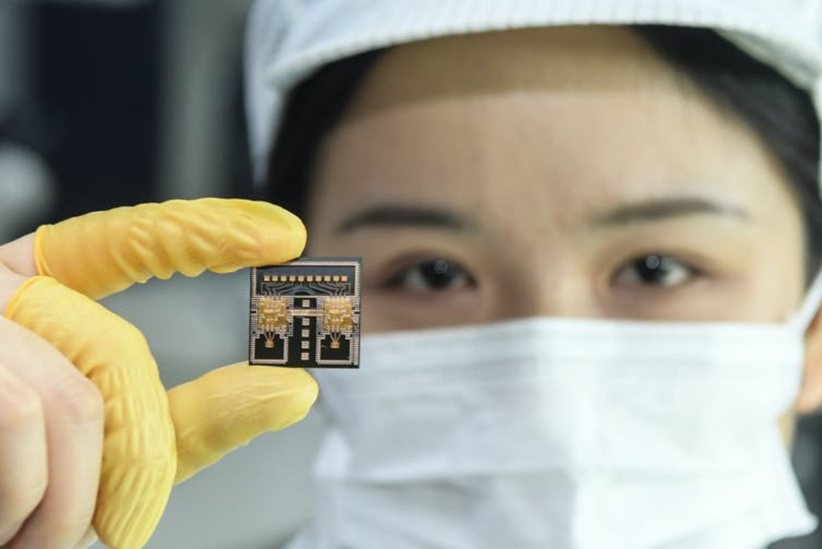 A worker in a Chinese research laboratory holds a chip used in automobile radar systems. Liu Yucai/Visual China Group via Getty Images