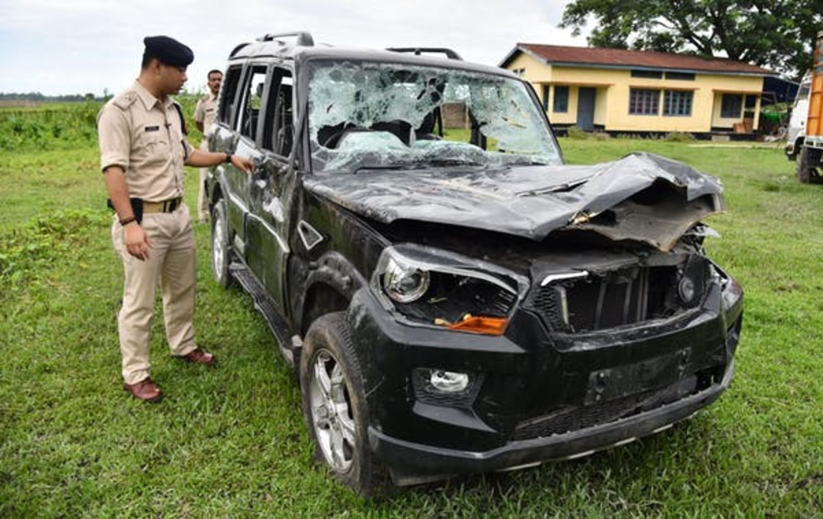 An Indian police officer inspects a damaged vehicle from which two men were taken and lynched by a mob afraid of strangers in their area because of misinformation spread on WhatsApp. Biju Boro/AFP via Getty Images