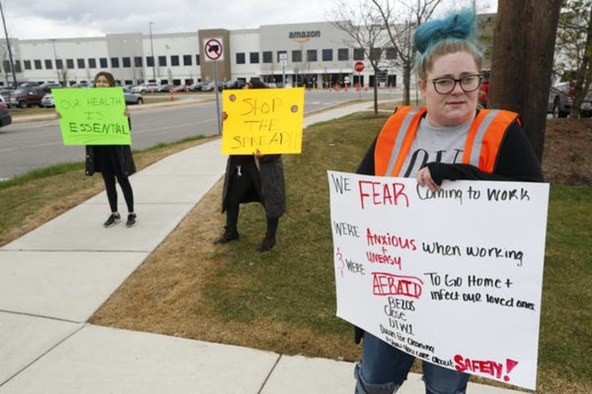 Amazon employees hold signs outside a fulfillment center in Romulus, Michigan. AP Photo/Paul Sancya
