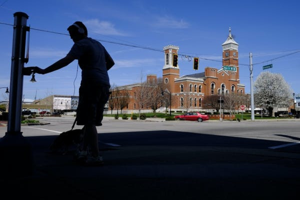 In Greensburg, Indiana, an empty town square, with only a teenager walking his dog. AP / Darron Cummings