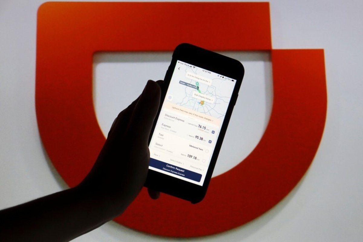 The Didi app seen on a mobile phone in front of the company logo on July 1. The ride-hailing firm's apps were removed from app stores in China following the launch of a cybersecurity investigation into the company. Photo: Reuters
