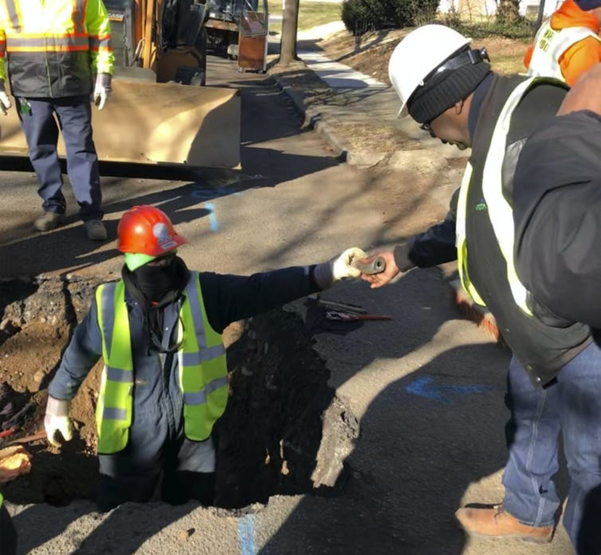 Workers remove water service lines in Trenton, New Jersey, on Jan. 9, 2020. The city is replacing 37,000 lead pipes over five years. AP Photo/Mike Catalini