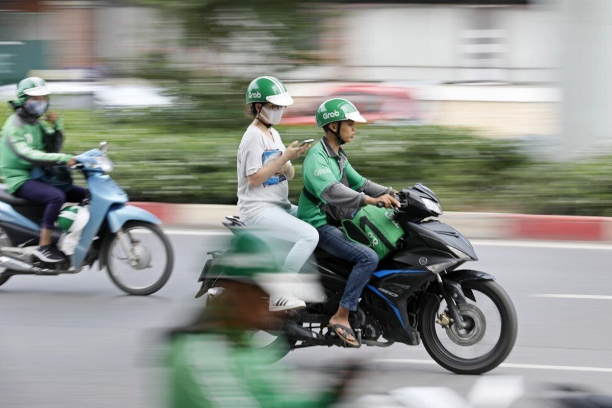 A GrabBike driver and his passenger in Hanoi in 2019. Photo: EPA-EFE