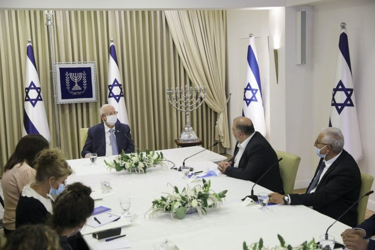 Mansour Abbas, leader of the Ra'am Party, second from right, and fellow Arab politician Mazen Ghanayem, right, discuss with Israeli President Reuven Rivlin who might form the next coalition government, at the president's residence in Jerusalem on April 5, 2021. Abir Sultan/Pool Photo via AP