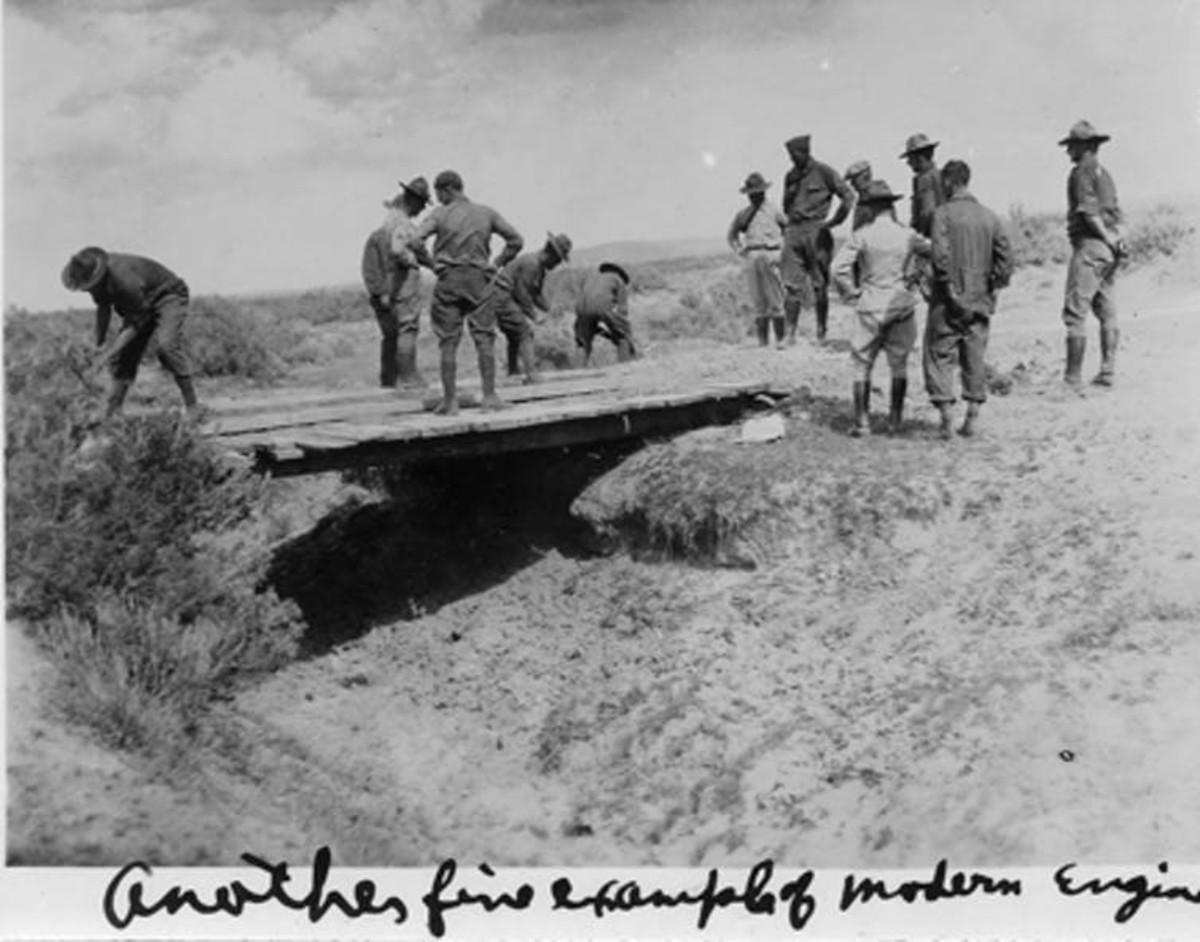 In a photo captioned 'Another fine example of modern engineering,' members of the 1919 Transcontinental Motor Convoy decide whether a rickety bridge will support their vehicles. Eisenhower Presidential Library
