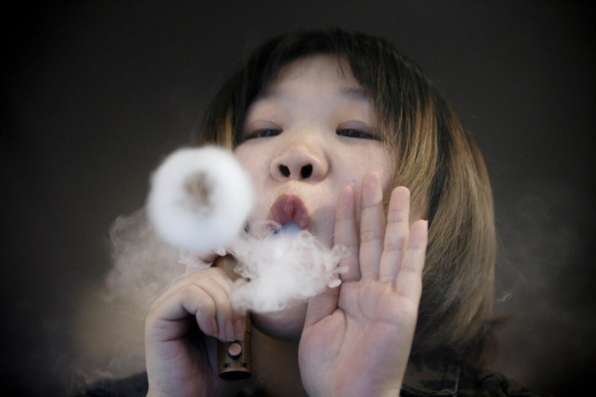 A saleswoman demonstrates vaping at the Vape Shop that sells e-cigarette products in Beijing in January 2019. Photo: Reuters