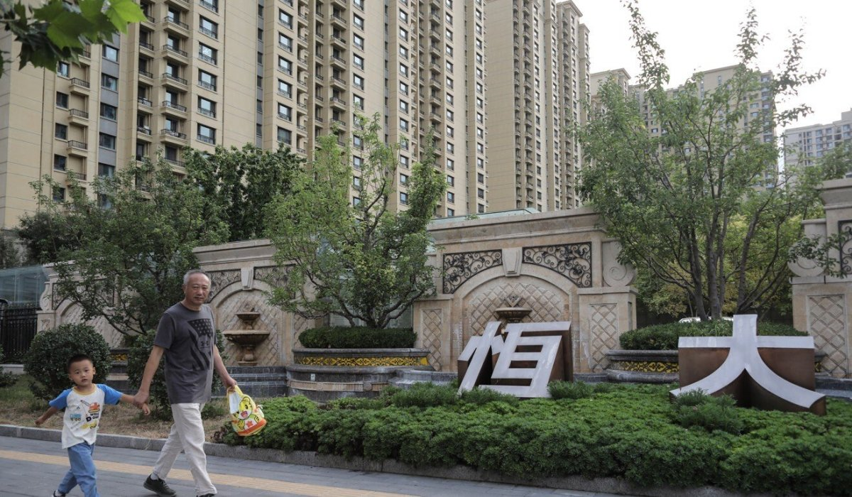 Residents walk near Evergrande's housing complex in Beijing. Sales at the company's projects have been hit because of worries over its debt. Photo: EPA-EFE